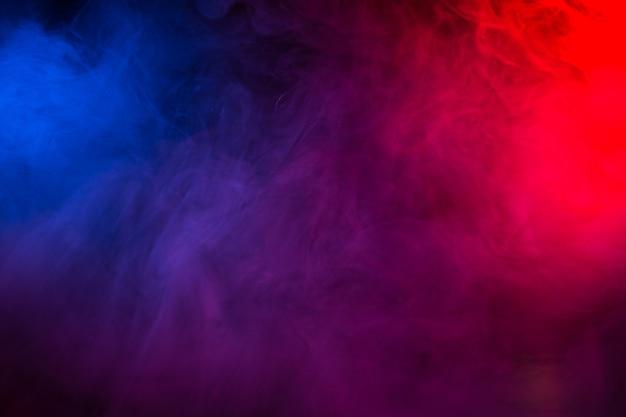 검은 배경에 구름 형태의 여러 가지 빛깔의 연기