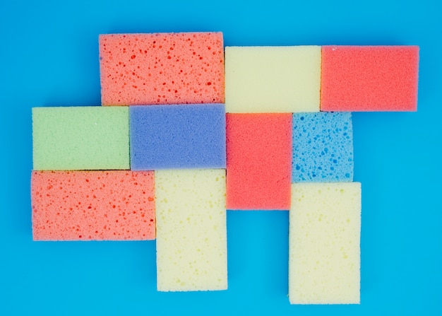 Multi colored sponges on blue background
