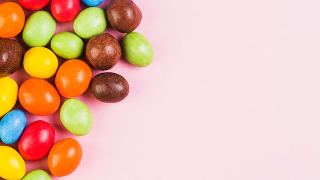 Multi colored sweet candies on pink background