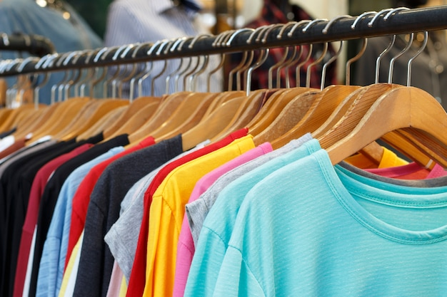 Multi-colored t-shirts with long sleeves on wooden hangers, side view.
