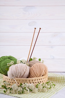 Multi-colored tangles of yarn in a wicker basket on the table. japanese style wabi sabi. home comfort, handicraft.