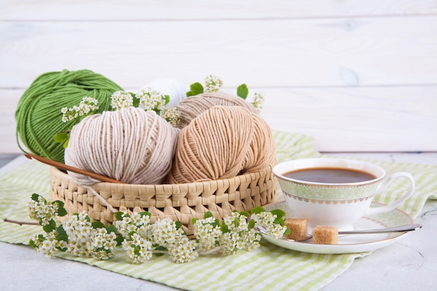 Multi-colored tangles of yarn in a wicker basket on the table. tea in a beautiful white cup. japanese style wabi sabi. home comfort, handicraft.