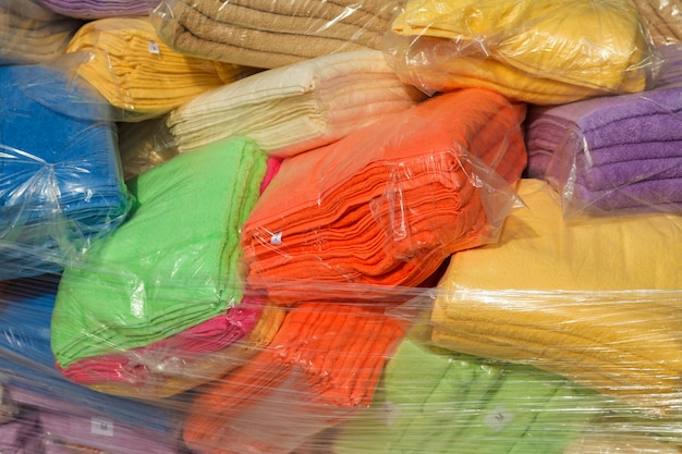 Multi-colored terry towels packed in plastic bags in stock