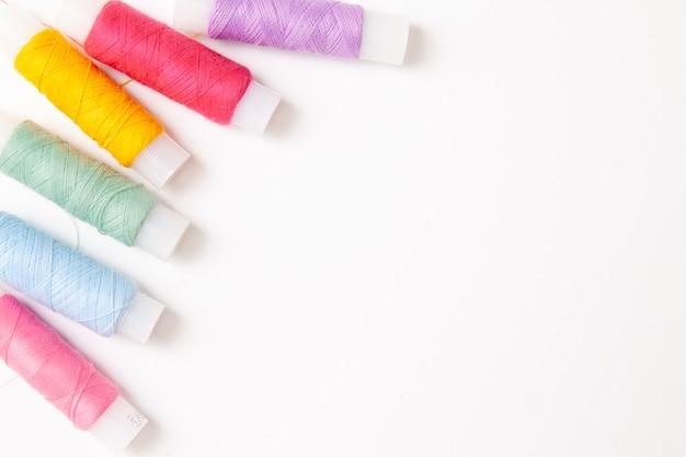 Multi colored thread coils on white.