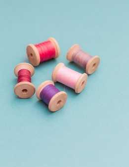 Multi-colored threads spools  on a blue sewing needlework embroidery handmade top view concept flat lay different differing variable