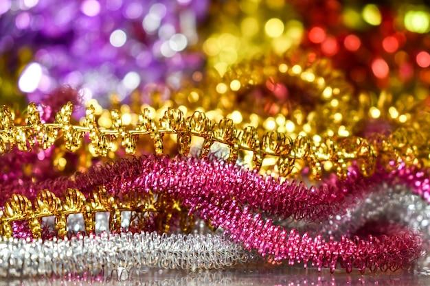 Разноцветная мишура на ярком размытом фоне боке. концепция рождественских и новогодних открыток.