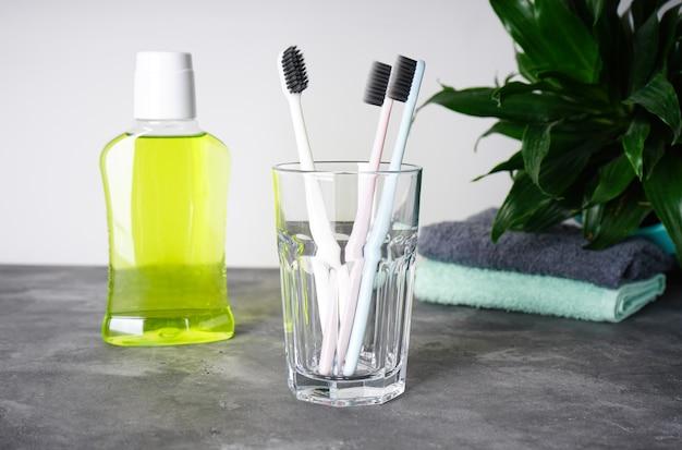 Разноцветные зубные щетки в стакане и жидкость для полоскания рта с цветком
