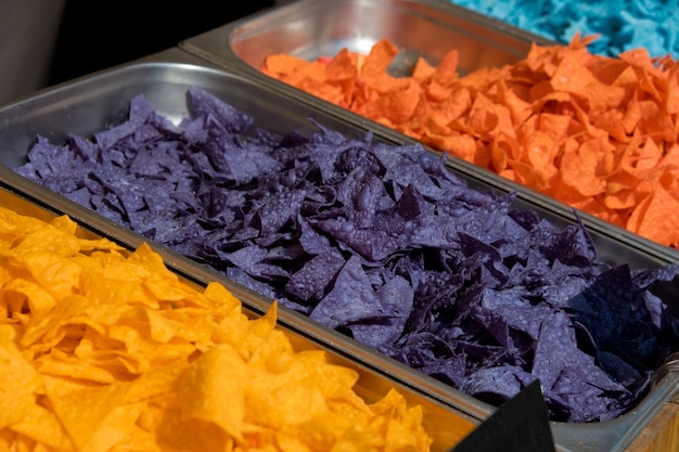 Multi colored tortilla chips in trays on the showcase. street food festival. selective focus.