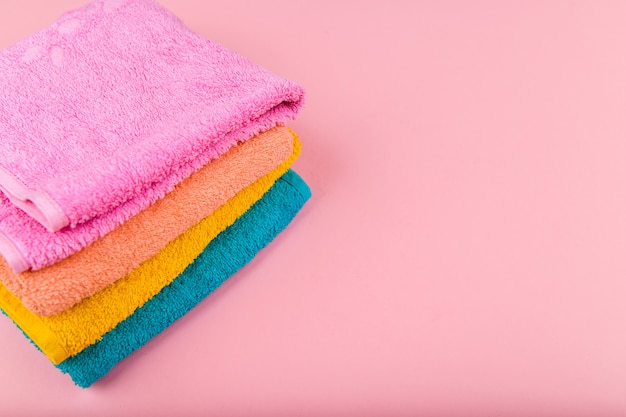 Multi-colored towels on a pink space. pink, beige, yellow and blue flower towels. place for writing. house order.