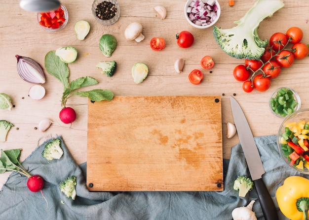 Multi colored vegetables surrounded near the wooden chopping board