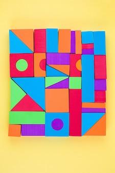 Multi-colored volumetric 3d geometric shapes on yellow