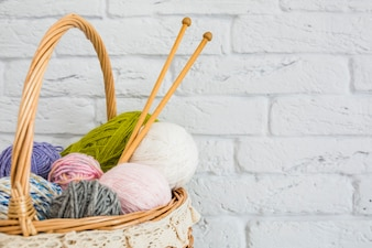 Multi colored yarns and crochet in wicker basket