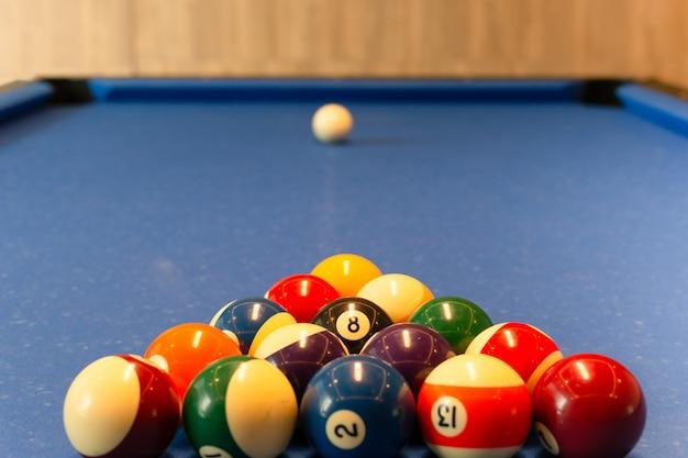 Multi colour billiard balls lie on the blue cloth table in the triangle.