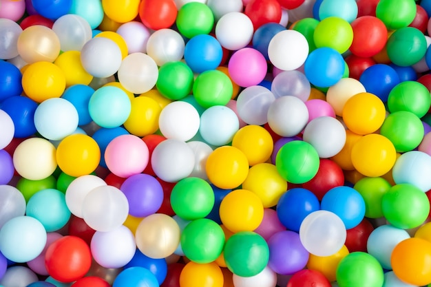 プレイセンターの大きなドライパドリングプールのマルチカラーのプラスチックボールをクローズアップ。プレイルーム。おもちゃ