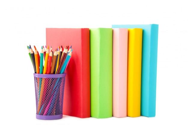 Разноцветные школьные учебники и карандаши, изолированные на белом