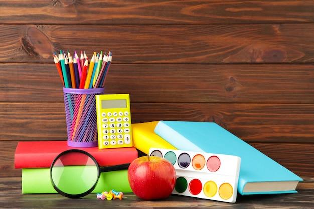 Разноцветные школьные учебники и канцтовары на коричневом дереве