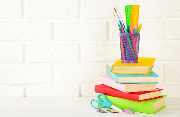 複数の色の教科書と白いレンガ壁の背景に文房具