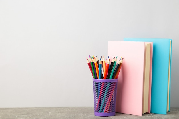 Multi coloured school books and pencils on grey