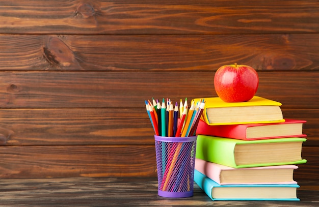 Multi coloured school books and stationery on brown wood