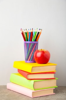 Multi coloured school books and stationery on grey background