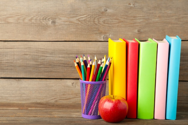 Multi coloured school books and stationery on grey wooden background