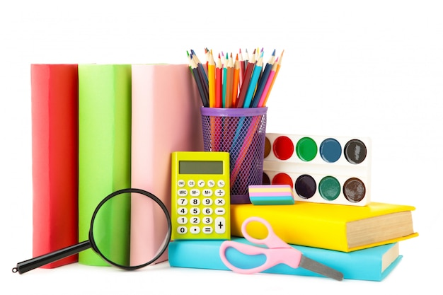 Multi coloured school books and stationery isolated on white background