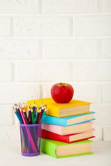 Multi coloured school books and stationery on white brick wall background