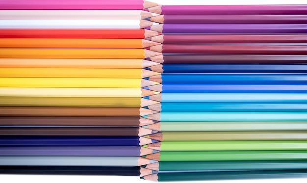 白い背景の上に鉛筆のマルチカラーセット。学校に戻る。描画、ペイント、学習の概念。フラットレイ