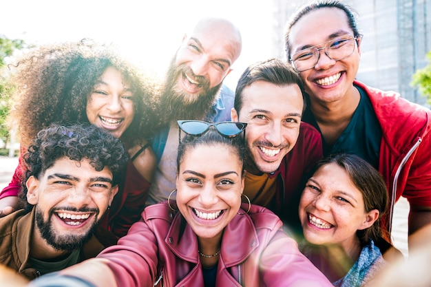 Multi cultural guys and girls taking selfie outdoors with backlight - happy milenial friendship concept on young multiracial friends having fun day together - bright vivid filter with sunshine flare
