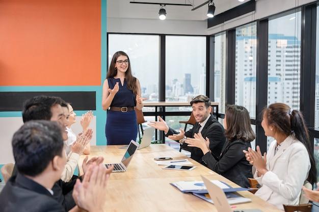Многонациональный деловой коллега, дружелюбный, обсуждает и встречается за столом для переговоров в современном офисе