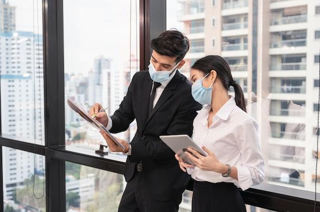 コロナウイルスコビッドのパンデミックの間、ビジネス地区の新しい通常のオフィスで話し合い、相談するフェイスマスクを身に着けている多民族のビジネス同僚