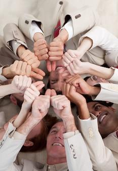 親指、床、上に横たわる多民族のビジネス人々