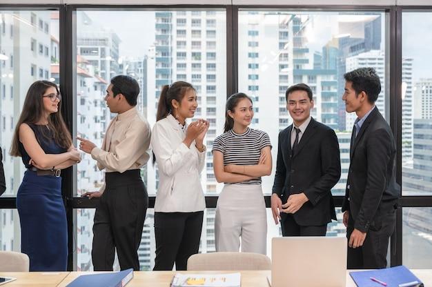 Коллега по многоэтнической бизнес-команде серьезно встречается и обсуждает у окна в современном офисе