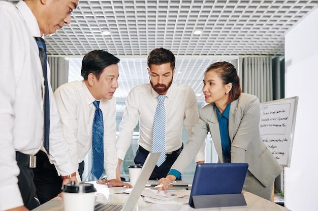 Многонациональная бизнес-команда обсуждает финансовые документы на встрече, предлагает новые идеи и проекты
