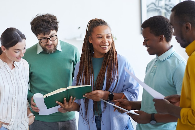 Многоэтническая бизнес-команда слушает улыбающуюся афроамериканку во время встречи в офисе