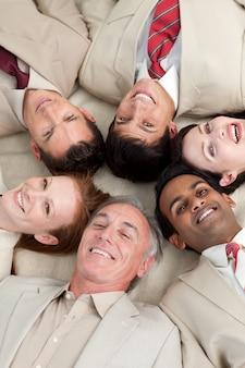 円の中に横たわる多民族のビジネスチーム