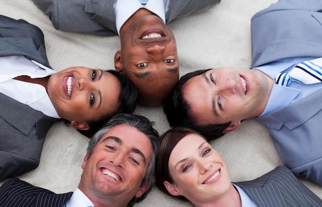 一緒に頭を持つ床に横たわる多民族のビジネスチーム