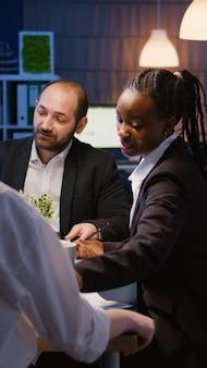 관리 프로젝트에서 과로하는 재무 그래프 프레젠테이션을 확인하는 사무실 회의실의 회의 테이블에 앉아 있는 다민족 비즈니스 팀. 회사 아이디어를 브레인스토밍하는 다양한 동료