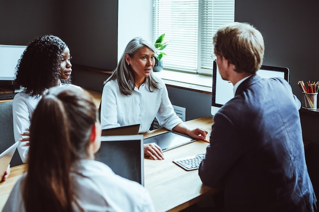 Многоэтническая бизнес-команда с компьютерами на встрече. руки деловых людей касаясь экрана электронного устройства. тонированное изображение. вид сбоку.