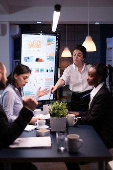 Multi-ethnic businesspeople discussing financial company solution sitting at conference table in meeting room