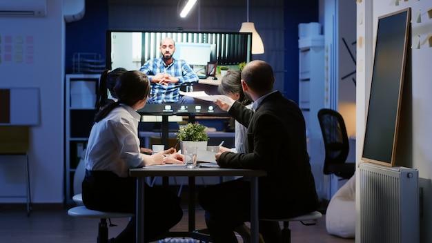 オンラインビデオ通話中に車椅子でリモート起業家と話し合う多民族のビジネスマン