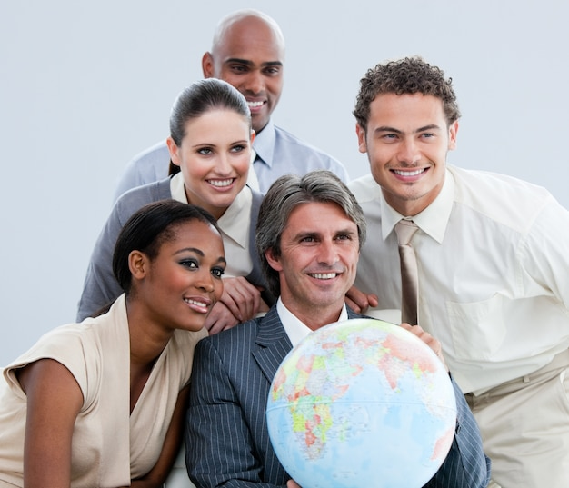 Multi-ethnic businessteam holding a globe in the office