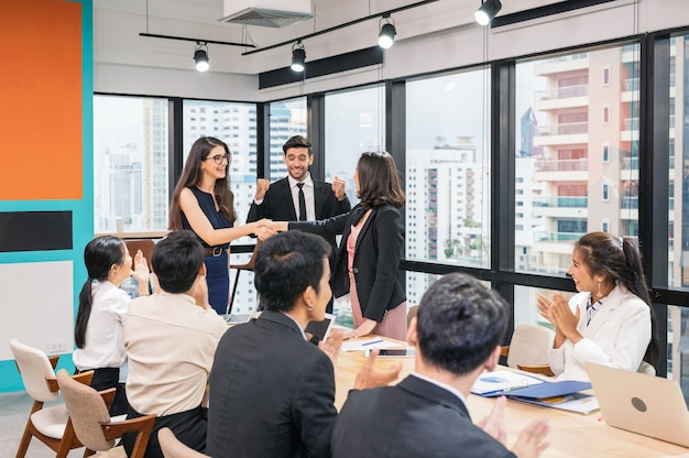 Multi ethnic businesswoman shaking hands cooperation for corporate agreement with coworkers in modern office