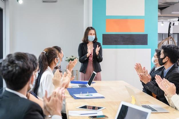新しい通常のオフィスで会う間、女性幹部を称賛して祝う多民族の同僚
