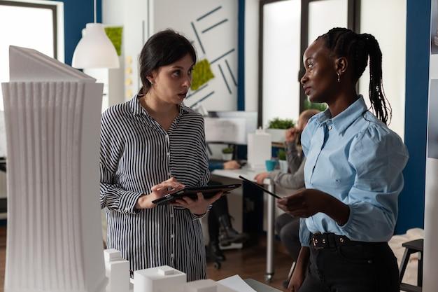 建設設計図計画マケットの建築作業計画について話し合う多民族の同僚。現代のエンジニアリング業界の建築モデルのビジョンを説明する女性のグループ