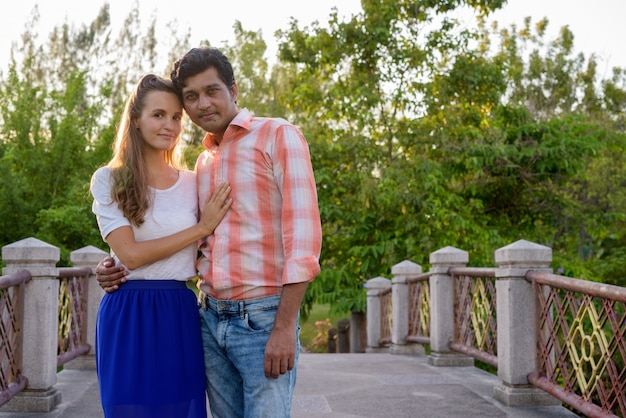 平和な緑豊かな公園の橋の上の愛の多民族のカップル
