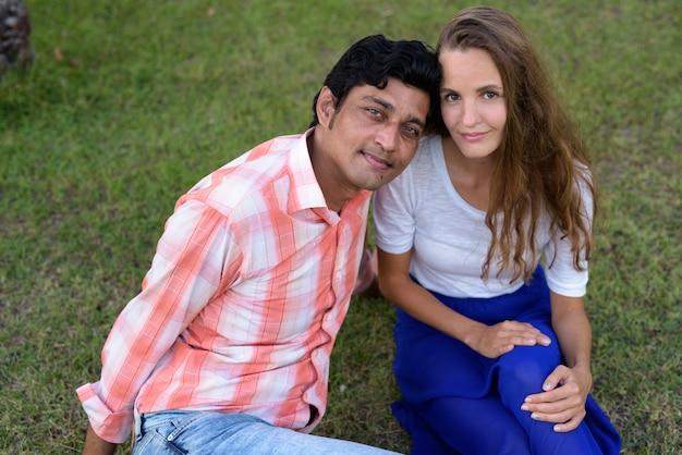 愛の牧草地に座っている多民族のカップル