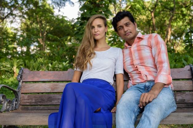 愛の木製ベンチに座っている多民族のカップル