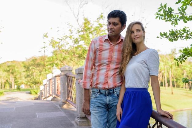 橋の上で一緒にそして愛を考えて多民族のカップル