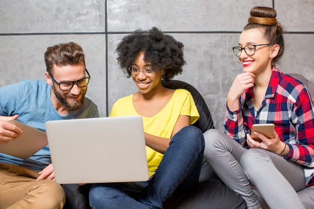 Multi ethnic coworkers dressed casually in colorful clothes working together with different gadgets sitting on the bag chairs on the gray wall background